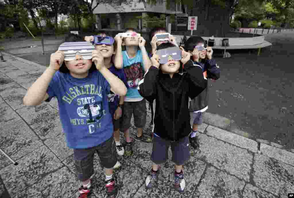 Los niños observan un eclipse solar anular en Fujisawa, Japón. .