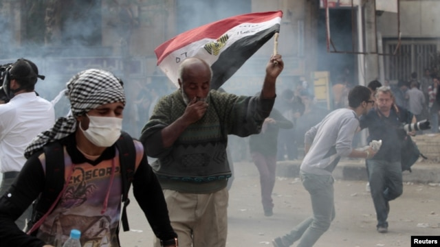 Anti-Morsi protesters run for cover during clashes with riot police at Tahrir Square in Cairo, November 27, 2012.