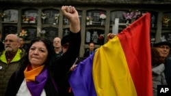 FILE - A woman holds up her left fist beside to a Spanish Republican flag during a tribute 46 unidentified people killed during the Spanish Civil War, at San Jose cemetery, Pamplona, northern Spain, April 1, 2019.