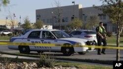 Un funcionario policial detiene un vehículo en un punto de control frente al centro de distribución de FedEx donde una explotó un paquete el martes, 20 de marzo, de 2018, en Schertz, Texas.
