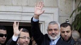 Le Premier ministre égyptien Hesham Kandil (à g.) salue la foule à Gaza City en compagnie du Premier ministre du Hamas, Ismail Haniyeh