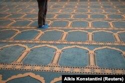 Seorang Muslim yang tinggal di Yunani mengenakan kaos kaki sebagai tindakan pencegahan terhadap penyebaran Covid-19 sebelum salat Jumat di masjid resmi pertama ibu kota, di Athena, Yunani, 6 November 2020. (Foto: REUTERS/Alkis Konstantini)