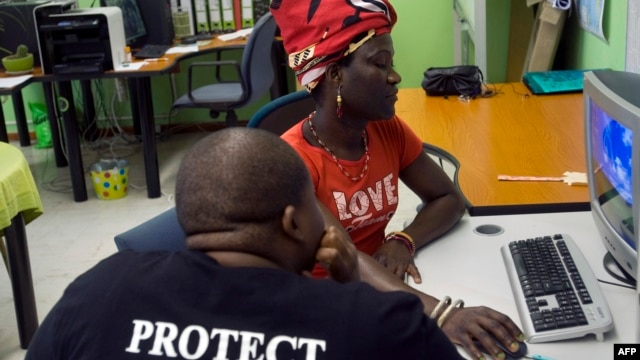 Malawian Tiwonge Chimbalanga (R) shares some of her experiences with Charlie Takati, outreach officer at the local charity Gender Dynamix, a gay rights organization, at their offices in Athlone, 15 kilometers from Cape Town, South Africa.