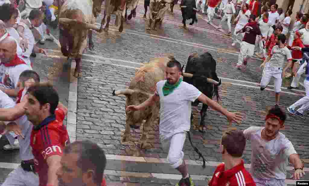 'سان فرمن' تہوار میں حصہ لینے والے افراد سانڈوں کے ساتھ دوڑتے ہوئے