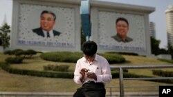 지난 2015년 5월 북한 평양의 김일성, 김정일 초상화 앞에서 한 남성이 스마트폰을 사용하고 있다. (자료사진)