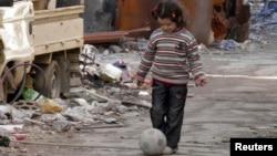 Bé gái chơi với quả banh trên đường phố hoang vắng của thành phố Homs đang bị bao vây, 30/1/14