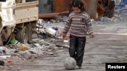Humus'un kuşatma altındaki bölgesinde top oynayan bir kız çocuğu