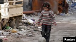 A girl plays with a ball along a street in the besieged area of Homs, January 30, 2014.