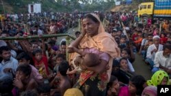 A Rohingya Muslim woman, who crossed over from Myanmar into Bangladesh, waits to receive aid with hundreds of other displaced Rohingyas, near Balukhali refugee camp, Bangladesh, Sept. 25, 2017.
