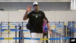 Mantan pemain basket NBA Dennis Rodman memberi isyarat kepada fotografer saat ia bersiap untuk pergi melalui imigrasi di Bandara Internasional Ibu Kota Beijing di Beijing, Selasa, 13 Juni 2017. (AP Photo/Mark Schiefelbein)