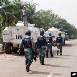 Des policiers onusiens originaires du Bangladesh passant à côté de Casques bleus jordaniens près du Golf Hotel, QG d'Alassane Ouattara à Abidjan