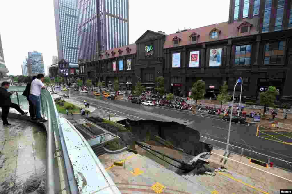 Warga mengamati bagian dari jalan raya yang ambles di kota Nantong, Jiangsu, China.