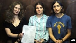 Pussy Riot members, from left, Maria Alekhina, Yekaterina Samutsevich, and Nadezhda Tolokonnikova show the court's verdict as they sit in a glass cage at a courtroom in Moscow, August 17, 2012.
