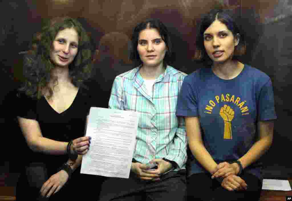 """2012年8月17日俄罗斯女庞克摇滚乐队""""Pussy Riot""""的三名歌手奥尔约其纳(图左),萨姆泽维奇(图中),和托洛尼克娃(图右)坐在俄罗斯一个法庭拘禁她们的玻璃隔离的角落,奥尔约其纳展示法院的判决书"""