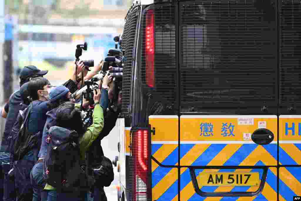 Members of the media surround a correctional services bus purportedly carrying pro-democracy activists Agnes Chow, Ivan Lam and Joshua Wong as it leaves the court in Hong Kong after the three pleaded guilty to inciting a rally during pro-democracy protests in 2019.