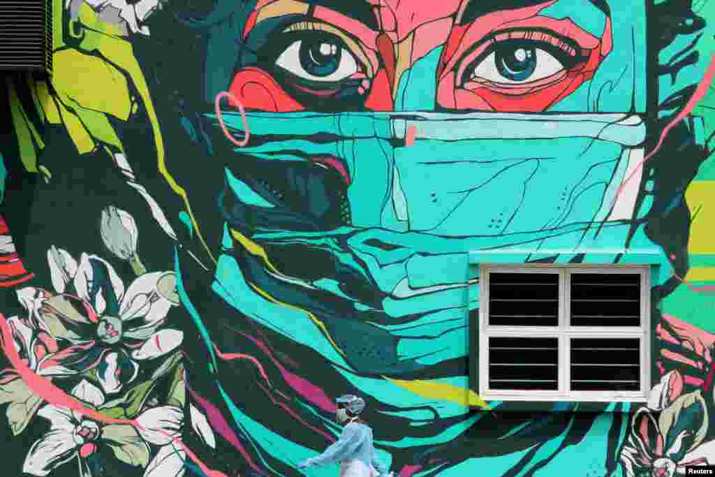 A medical worker wearing personal protective equipment passes by a frontliner mural outside a clinic, amid the coronavirus outbreak in Kuala Lumpur, Malaysia.