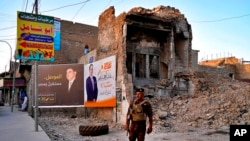 FILE - An Iraqi federal policeman stands guard near campaign posters for parliamentary elections that are displayed near destroyed buildings from fighting between Iraqi forces and the Islamic State group in Mosul, Iraq, Oct. 3, 2021.