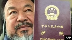 This handout picture released by Chinese dissident artist Ai Weiwei on July 22, 2015 shows Ai Weiwei posing with his passport in Beijing.
