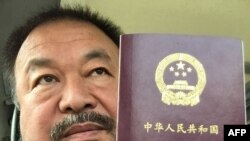 FILE - This handout picture released by Chinese dissident artist Ai Weiwei on July 22, 2015, shows him posing with his passport in Beijing.