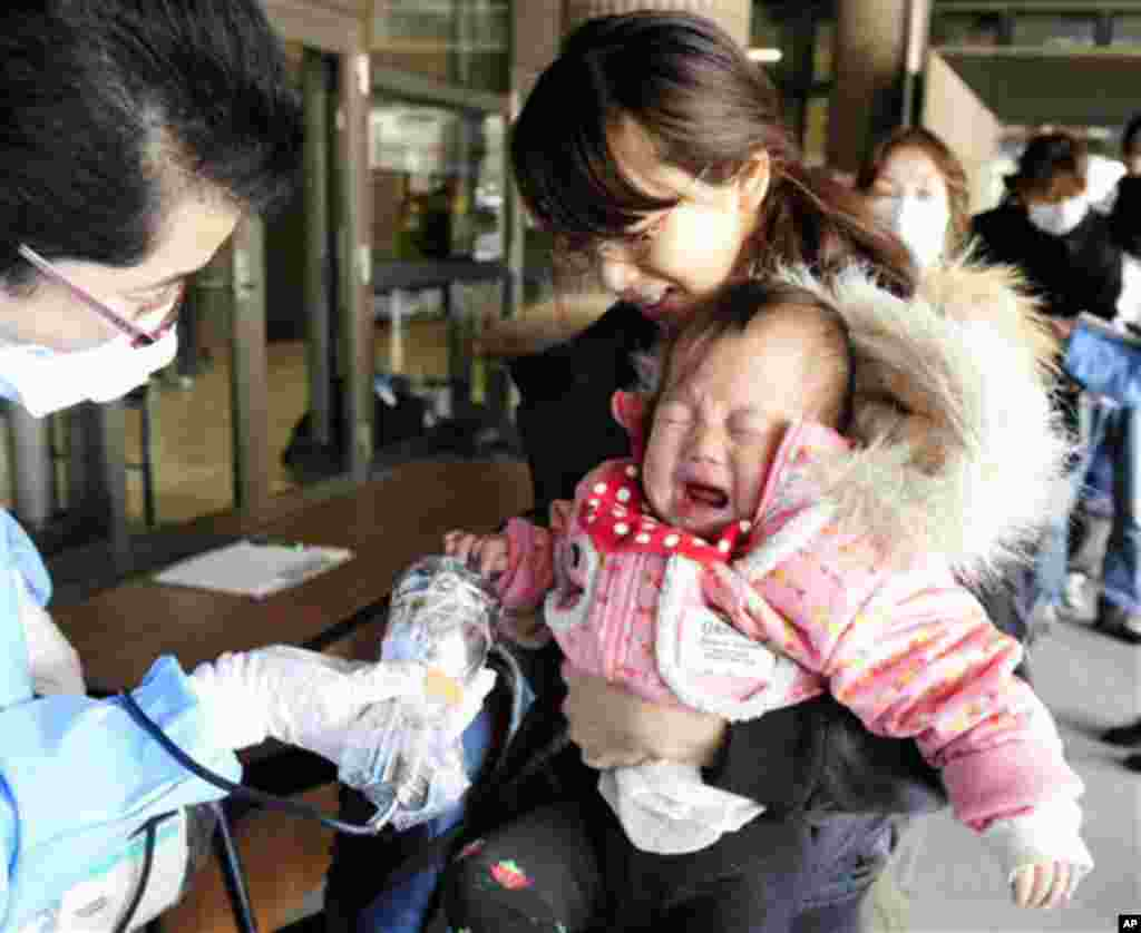 A baby cries as she is helped by her mother to be screened for radiation exposure before entering an evacuation center in Fukushima. (AP Image)