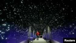 FILE - New York's climate change museum will have only two rivals. One is the Klimahaus (Climate House) in Bremerhaven, Germany. In one of its exhibits, shown above, a man looks at an artificial starry sky.