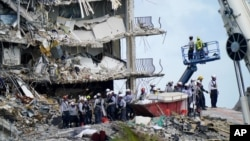 Spasilačke ekipe pretražuju ruševine zgrade u Surfsideu. (Foto: AP/Lynne Sladky)