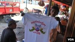 """若开邦抗议联合国和NGO的人士向记者展示参加游行的统一服装,T恤上面写着:""""守卫西门不被破坏。""""(美国之音朱诺拍摄,2013年11月13日)"""