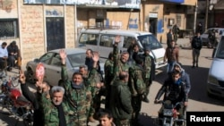 FILE - Fighters loyal to Syria's President Bashar al-Assad celebrate with residents of Nubul and al-Zahraa after breaking the siege of their towns in the northern Aleppo countryside, Syria, in this handout picture provided by SANA, Feb. 4, 2016.