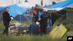 希腊警察在伊多梅尼临时难民营执行任务。