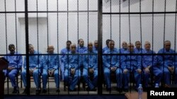 Officials of Moammar Gadhafi's government, including Abdullah al-Senussi (L), ex-spy chief in Moammar Gadhafi's government and Buzeid Dorda (2nd L), ex-intelligence chief, sit behind bars during a hearing at a courtroom in Tripoli, April 14, 2014.