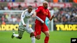 Jonathan de Guzman, kiri, dari Klub Swansea berusaha merebut bola dari Jose Enrique dari klub Liverpool dalam pertandingan Liga Premier hari Minggu (25/11).