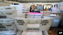 Election workers scan mail-in and absentee ballots for the 2020 general election in the United States at West Chester University, Wednesday, Nov. 4, 2020, in West Chester, Pa. (AP Photo/Matt Slocum)