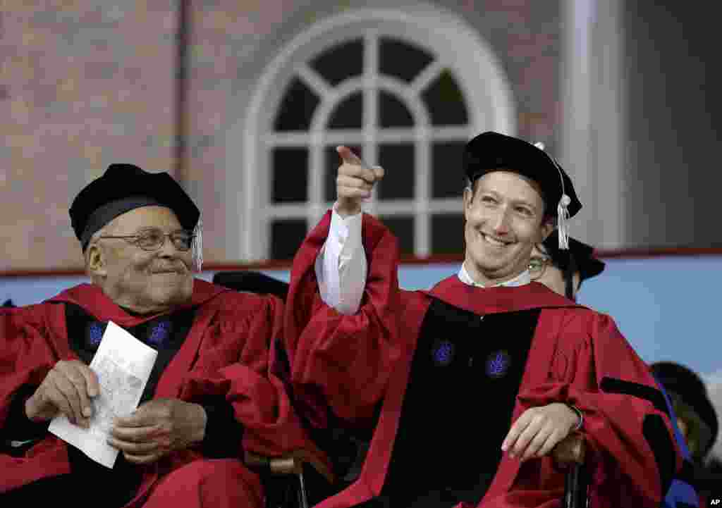 Facebook CEO and Harvard dropout Mark Zuckerberg, right, gestures as actor James Earl Jones, left, looks on while seated on stage during Harvard University commencement exercises, in Cambridge, Massachusetts. Zuckerberg was presented with an honorary Doctor of Laws degree and gave a commencement address.