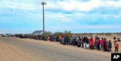 This Jan. 14, 2019, photo released by U.S. Customs and Border Protection shows some of the 376 Central Americans the Border Patrol says it arrested, the vast majority of them families who had dug holes to cross into the United States, about 10 miles east of San Luis, Ariz.