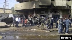Petugas keamanan menginspeksi lokasi ledakan bom mobil, yang meledak saat berlangsungnya perayaan keagamaan Syiah di Baghdad (13/6).