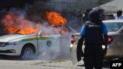 نائیجیریا کے دارالحکومت ابوجا میں ایک پولیس اہل کار جلتی ہوئی گاڑی کو دیکھ رہا تھا۔ ابوجا میں مظاہرین پر پولیس فائرنگ سے متعدد افراد ہلاک ہو گئے تھے۔ 30 اکتوبر 2018