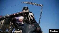 Người biểu tình cầm hình ảnh mô tả Tổng thống Nga Vladimir Putin trong một cuộc biểu tình chống chiến tranh tại Quảng trường Độc lập ở Kiev, ngày 23/4/2014.