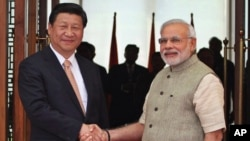 FILE - Indian Prime Minister Narendra Modi, right, shakes hand with Chinese President Xi Jinping as he welcomes him at a hotel in Ahmadabad, India, Sept. 7, 2014. The two leaders will meet April 27-28, 2018, for a visit that some experts have described as a possible way to reset a complicated relationship between the two Asian powers.