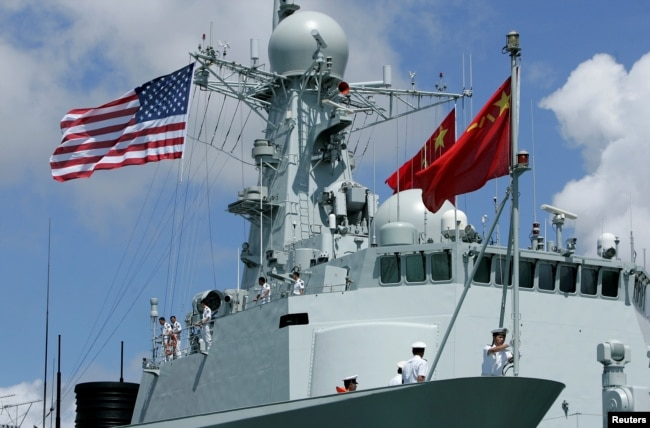 FILE - A sailor in China's People's Liberation Army Navy hoists the Chinese flag after arriving at the Joint Base Pearl Harbor Hickam to participate in the multinational military exercise RIMPAC in Honolulu, Hawaii, June 29, 2016.