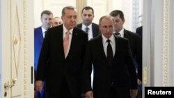 Presiden Rusia Vladimir Putin (kanan) menyambut tamunya, Presiden Turki Recep Tayyip Erdogan sebelum pertemuan di St. Petersburg, Rusia, Selasa (10/8).