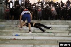 Povređeni demonstrant leži na stepenicama ispred Doma Narodne skuopštine Srbije, tokom sukoba policije i demonstranata, u Beogradu, 7. jula 2020. (Foto: Rojters, Marko Đurica)