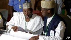 尼日利亚独立的全国选举委员会主席杰加(左)正在审视选票。3月30日摄于首都阿布贾。