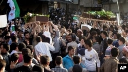 In this Saturday, April 21, 2012 photo, Syrians carry the bodies of an infant, Adam al Najjar, and Free Syrian Army fighter, Mowaffaq al Nablsi, 42, during their funeral in Douma, a suburb of Damascus, Syria.
