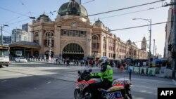 Seorang polisi berpatroli dengan sepeda motor di Melbourne, 12 Februari 2021, setelah pihak berwenang memerintahkan lockdown selama lima hari di seluruh negara bagian mulai tengah malam waktu setempat untuk mencegah penyebaran virus COVID-19. (Foto oleh Con Chronis / AFP)