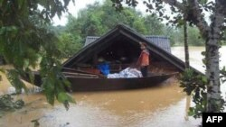 Một bé gái đứng trên chiếc thuyền ở phía trước ngôi nhà bị ngập ở Hà Tĩnh, ngày 5/10/2010. Tỉnh bị thiệt hại nhân mạng nặng nhất là Quảng Bình, với hơn 10 người chết. Nghệ An, Hà Tĩnh và Quảng Trị cũng bị thiệt hại nặng