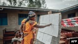 Une femme cherche son nom sur son lieu de vote avant de voter dans le quartier Kasanga-Ndindi de Beni le 31 mars 2019. (Photo: Luke DENNISON / AFP)