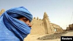 Nómada tuaregue ao lado da centenária mesquita de Tumbouctou no norte do país
