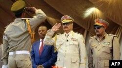 Le maréchal Khalifa Haftar, au centre, salue le chef d'état-major de l'armée nationale libyenne Abdelrazak al-Nadhuri, à droite, et l'ancien Premier ministre libyen Abdullah al-Thani, chef du gouvernement à Bayda, lors d'une parade militaire à Benghazi, Libye, le 7 mai 2018.