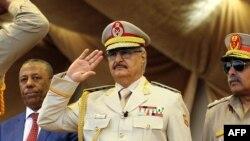 Le maréchal Khalifa Haftar, au centre, salue le chef d'état-major de l'armée nationale libyenne Abdelrazak al-Nadhuri, à droite, et l'ancien Premier ministre libyen Abdullah al-Thani, chef du gouvernement à Bayda, lors d'une parade militaire à Benghazi, L