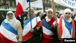 Perempuan Muslim yang mengenakan bendera Perancis berbaris di Paris saar protes undang-undang baru yang melarang simbol-simbol agama di sekolah-sekolah negeri Prancis, 14 Februari 2004. (Foto: Reuters)